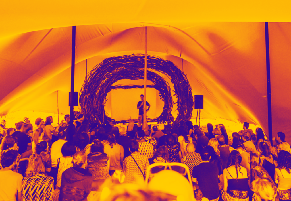 man speaking to crowd noisily festival